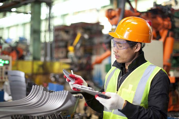 Image of a man checking a list in a factory.